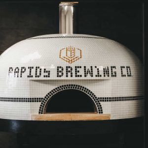 Tiled wood-fired oven with Rapids Brewing Company logo